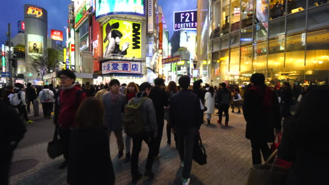 camera is walking through the shibuya intersection to go to shibuya center gai street on sunday evening at dusk. and captures the night cityscape and pedestrians while walking. - 交差点点の映像素材/bロール