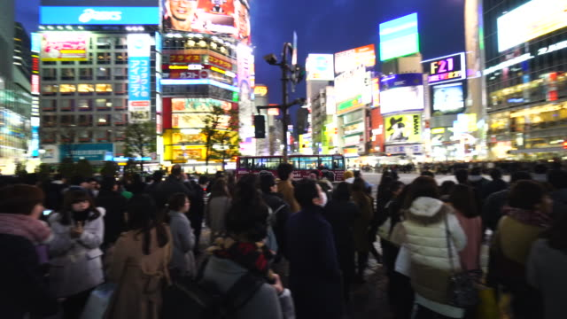 camera is walking through the shibuya intersection to go to shibuya center on sunday evening at dusk.and captures the night cityscape and pedestrians while crossing the intersection. - waiting stock videos & royalty-free footage