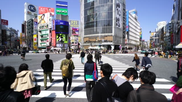 camera is walking through the shibuya intersection to go to shibuya center on sunday afternoon.and captures the cityscape and pedestrians, while crossing the intersection. - tracking shot stock videos & royalty-free footage