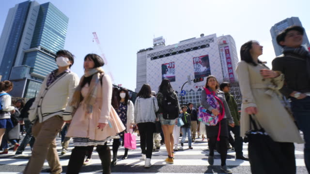 vídeos de stock, filmes e b-roll de camera is walking through the shibuya intersection to go to shibuya station on sunday afternoon. .and captures the pedestrians, cityscape and shibuya station while crossing the intersection. - cruzando
