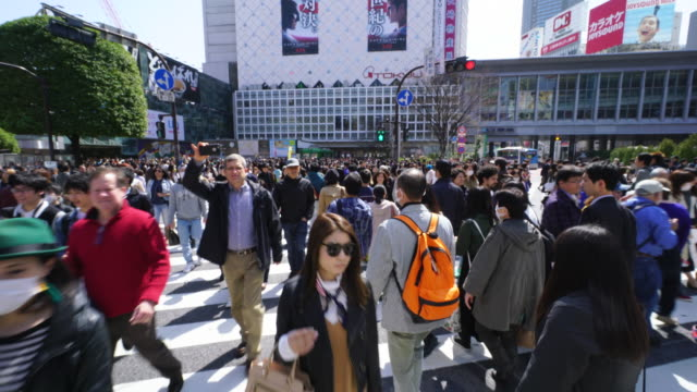 Camera is walking through the Shibuya Intersection to go to Shibuya Station on Sunday afternoon. And Captures the pedestrians, cityscape and Shibuya Station while crossing the intersection.