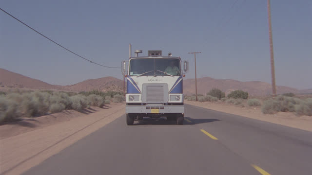 camera leads semi truck straight to camera, hold on cab; sev'l views - articulated lorry stock videos & royalty-free footage