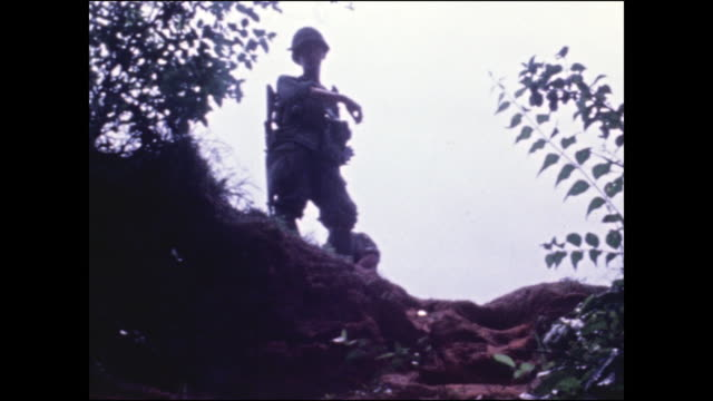 camera looks back up at soldier standing above the entrance and looking down at the camera / us and south vietnamese soldiers. - south vietnam stock videos & royalty-free footage