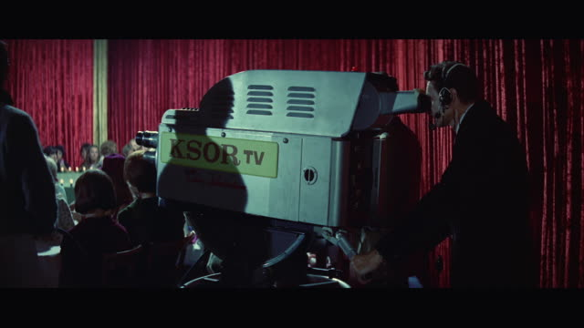 1967 ms pan camera man operating large television camera, audience in background - fernsehserie stock-videos und b-roll-filmmaterial