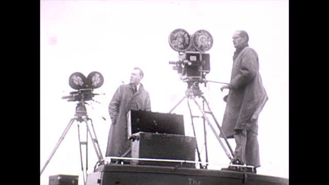 camera men located on top of cars 1938 various shots of two camera men one with a pipe pan to their subject at an outdoor motor racing event possibly... - anno 1938 video stock e b–roll