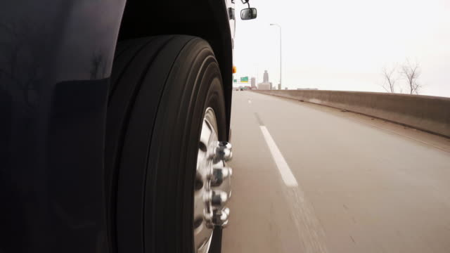 pov camera mounted at front right tire of large commercial semi truck or bus; traveling west on interstate 480 west toward the omaha skyline in winter. - omaha stock videos & royalty-free footage
