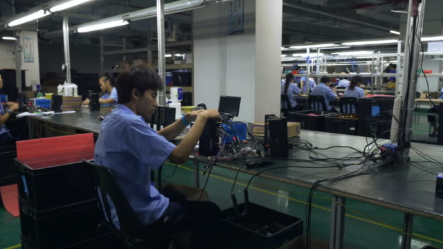 A camera mounted onto an electronics assembly line pans left to reveal a number of Chinese workers assembling GPS units and circuit boards