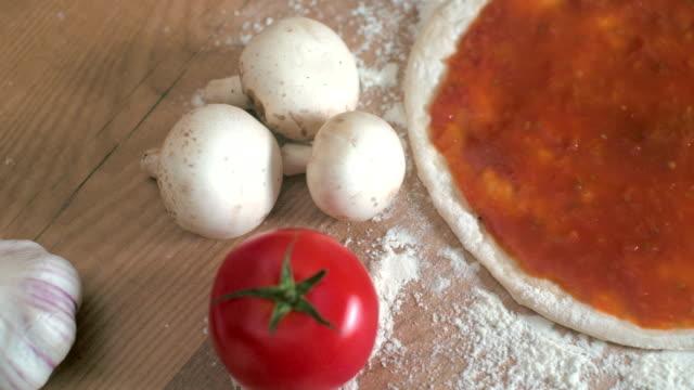 Movimento della telecamera con salsa di pomodoro sulla pizza base