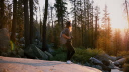 Camera moves around excited tourist girl standing on big rock in deep woods of Yosemite on incredible sunset slow motion