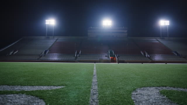 slo mo. camera moves back over 50 yard line of football field in empty stadium. - back lit stock-videos und b-roll-filmmaterial