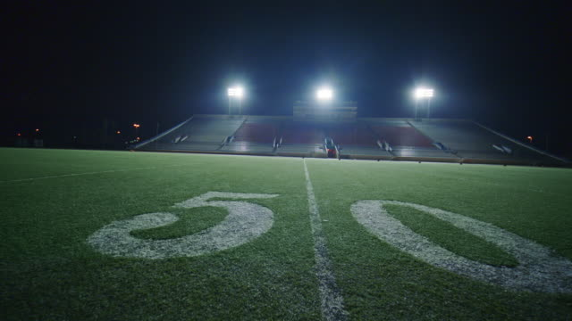 SLO MO. Camera moves back over 50 yard line of football field in empty stadium.