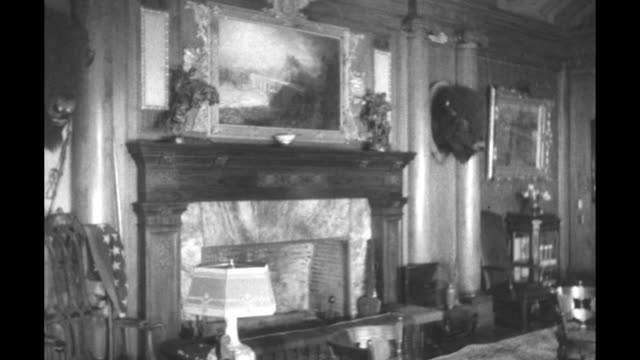 Camera moves forward into living room between pair of elephant tusks / close shot of painted portrait of Theodore Roosevelt hanging on wall of living...