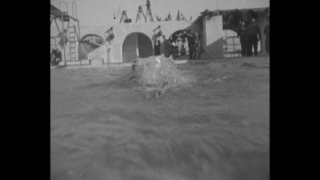 pov camera moves in front of a woman swimming at pool with a wall and arches behind her / note exact day not known - 1930 stock videos & royalty-free footage