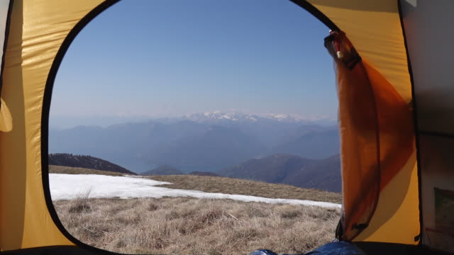 camera moves through tent window to view of mountains and grass pasture - tent stock videos & royalty-free footage