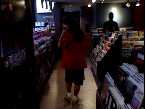 camera moves through the aisles of a tower records store as people browse the shelves for music - tower records stock videos & royalty-free footage