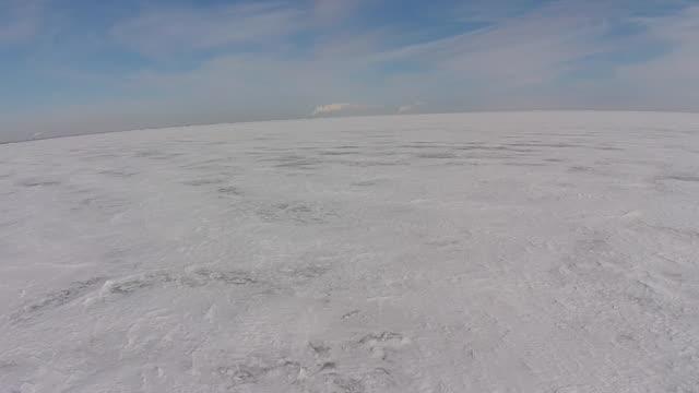 stockvideo's en b-roll-footage met camera moving backwards over frozen lake erie ice on to shore - eriemeer