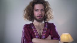 Camera moving from left to right around young bearded Caucasian man with long curly hair and brown eyes looking at camera and smiling. Portrait of positive intersex person standing with hands crossed.