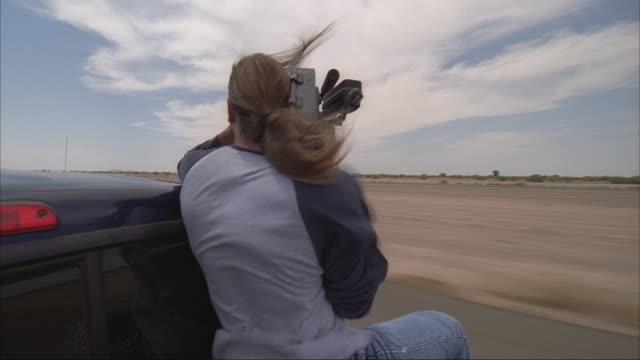 a camera operator films a skydiving plane taking off. - テレビカメラ点の映像素材/bロール