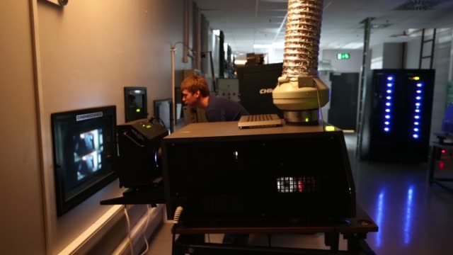 stockvideo's en b-roll-footage met camera operator monitors a movie screening in the projection room of a cinema park multiscreen theatre complex at the metropolis shopping and... - filmscreening