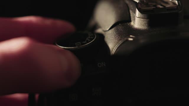 camera operator turning on dslr and selecting shooting mode - デジタル一眼レフカメラ点の映像素材/bロール