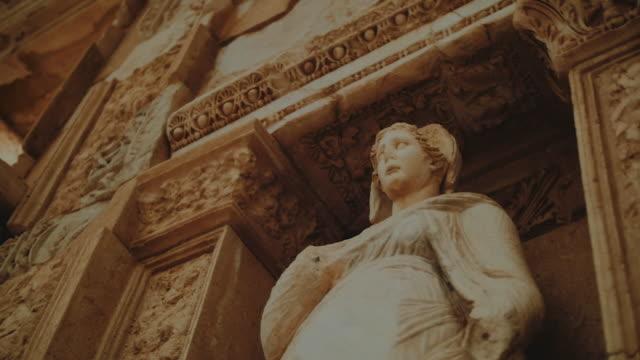 vídeos y material grabado en eventos de stock de camera pan around ancient statue in library of celsus - roma antigua