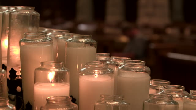 vídeos y material grabado en eventos de stock de camera pan from prayer candles to a defocused man praying inside of saint paul cathedral in pittsburgh, pennsylvania on august 15, 2018. - religion or spirituality