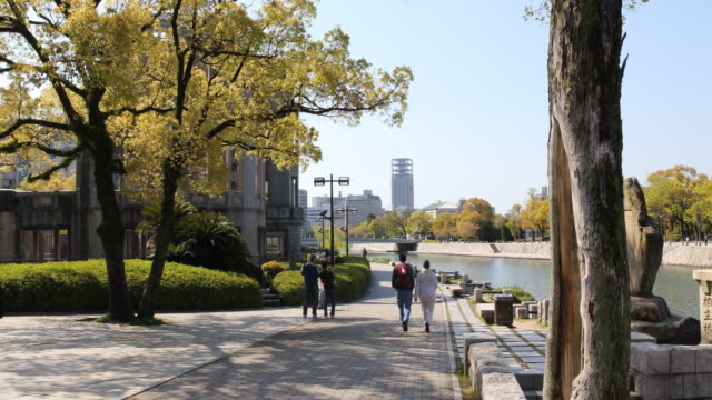 A camera pan to the left showing a paved walkway at the Hiroshima Peace Memorial on the Motoyasu riverside and visitors standing behind the ruined...