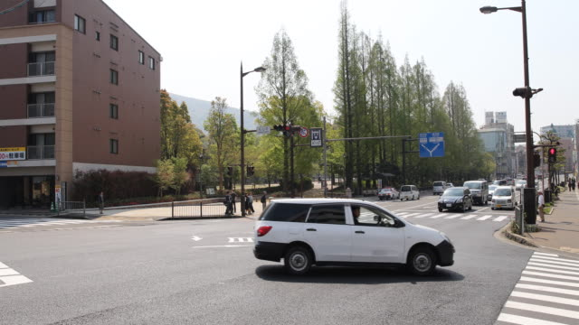 camera pan to the left, showing a street crossing during daytime in nagasaki next to the cenotaph memorial at the hypocenter in nagasaki. - road signal stock videos & royalty-free footage