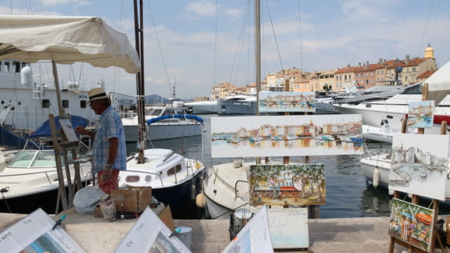 a camera pan to the left showing paintings with sailing motives on display and an artist while painting at his stand on the promenade tourist are... - painting art product stock videos & royalty-free footage