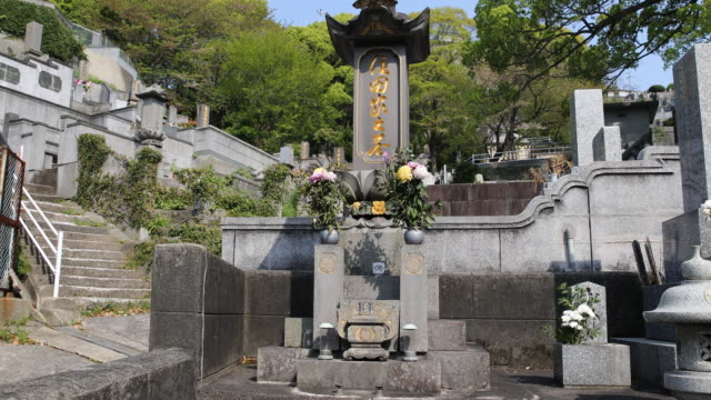 vidéos et rushes de camera pan to the right, showing a memorial monument with marbled headstones and golden inscriptions in japanese - arme de destruction massive