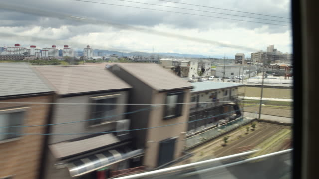 a camera pan to the right showing the view of a passing landscape seen through the window of the express train on the japanese island kyushu close to... - kyushu shinkansen stock videos & royalty-free footage