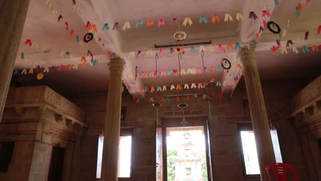 camera panning from the ceiling hanging with garlands to the red stone floor opposite the exit of a catholic church founded by jesuits on both sides... - christian ender stock-videos und b-roll-filmmaterial