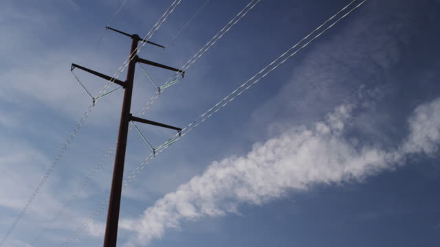Camera pans across a large electrical tower with large wires looming against a blue sky and white clouds.