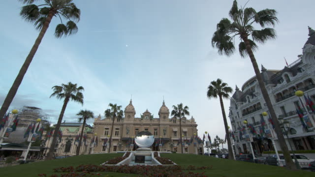 camera pans across casino de monte-carlo square to reveal the casino and the mirror sculpture 'sky mirror' by anish kapoor - monaco stock-videos und b-roll-filmmaterial