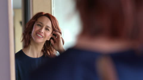 camera pans across smiling, middle-aged woman running hand through red hair and looking at self in mirror. - mature women stock-videos und b-roll-filmmaterial