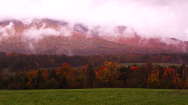 Camera pans across vista of Vermont mountains covered in Fall colors.