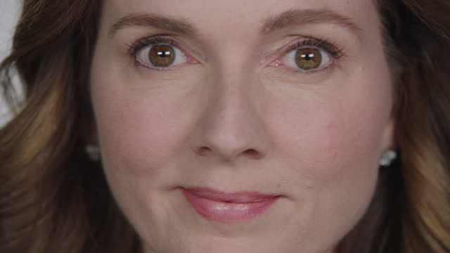 CU SLO MO. Camera pans as woman stares and blinks at camera in white studio.