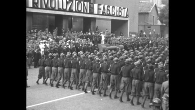 camera pans down front of large building to black shirt boys marching past crowd and mussolini on viewing stand, sign reading in part òdella... - benito mussolini stock videos & royalty-free footage