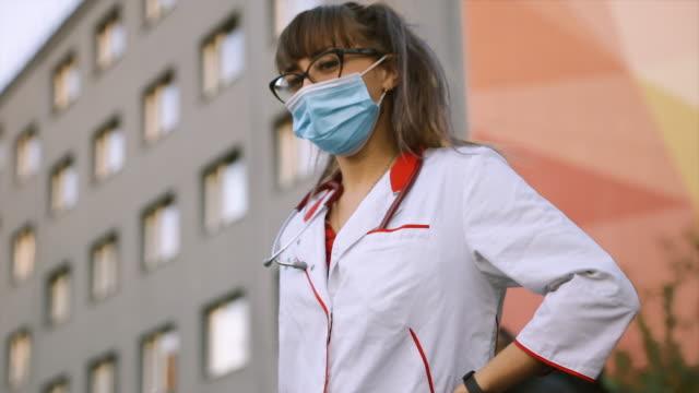 vídeos de stock, filmes e b-roll de camera pans from lgbt rainbow bracelet up to young female doctor's face in medical mask - estudante universitária