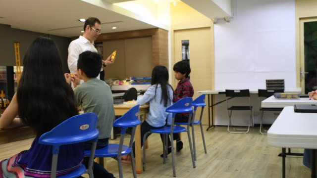 camera pans from teacher to students in stem class - elementary school stock videos and b-roll footage