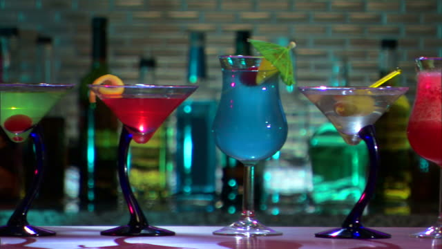 stockvideo's en b-roll-footage met camera pans left across colorful cocktails on bar. - martiniglas