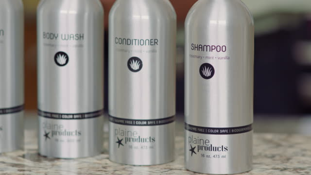 camera pans left and right across aluminum bottles of eco-friendly shampoo, conditioner, body wash and lotion in television infomercial. - shampoo per capelli video stock e b–roll