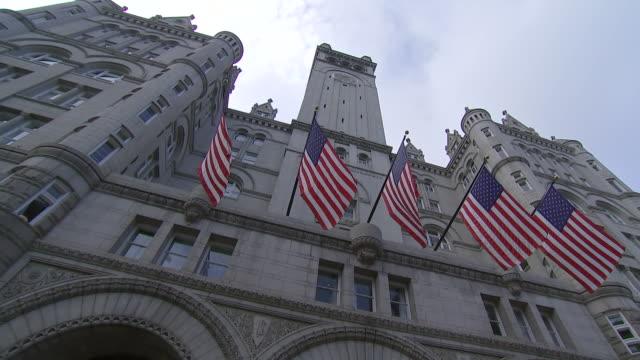 vídeos de stock, filmes e b-roll de camera pans left as american flags hang outside trump international hotel on pennsylvania avenue, nw in washington dc - pennsylvania avenue