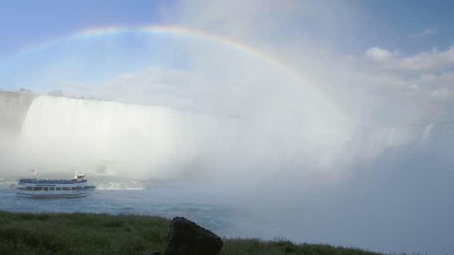 camera pans left revealing beautiful rainbow over maid in the mist tour boat beneath the mist of niagara falls. - ナイアガラ滝点の映像素材/bロール