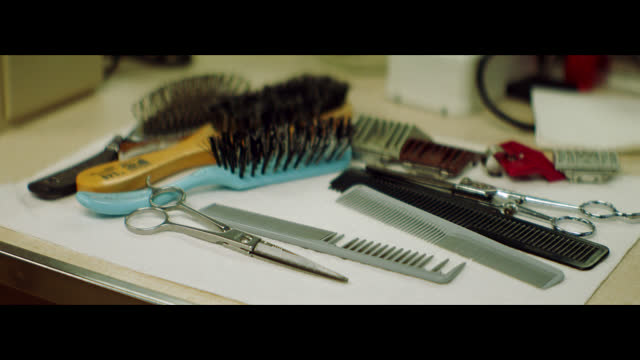 stockvideo's en b-roll-footage met camera pans over barber shears, combs, and brushes arranged on a counter in a small town barber shop. - haarborstel