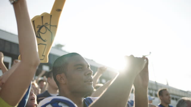 camera pans over football fans celebrating in crowded stadium as they high five and cheer for their favorite team. - foam hand stock videos and b-roll footage