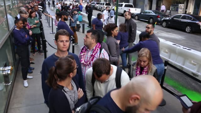 camera pans over line of people waiting outside the apple store at 5th ave and 58th street in midtown manhattan during launch of iphone 8 apple tv 4k... - launch event stock videos & royalty-free footage