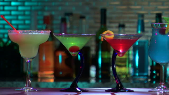 stockvideo's en b-roll-footage met camera pans right across colorful cocktails on bar. - martiniglas
