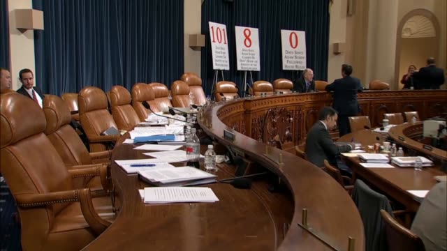 camera pans right from empty seats on the committee dais to reporters gathered around to witness table during the seventh open impeachment hearing of... - witness stock videos & royalty-free footage