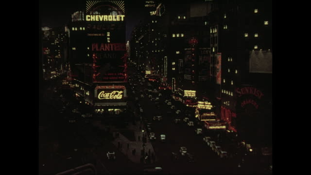 1937 Camera pans the cityscape of Times Square at night